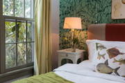 A bedside table lights an eclectic guest room