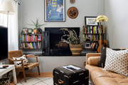Living room detail with bookshelves, a leather sofa, and globally inspired grasscloth accents.