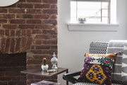 Mixed patterns pop against white walls and an exposed brick fireplace