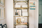 A brass shelf crowned by two blue ginger jars