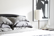 Black and white framed art hanging beside grey and white bed.
