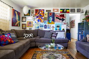 A living area with walls filled with paintings and a corner sofa.