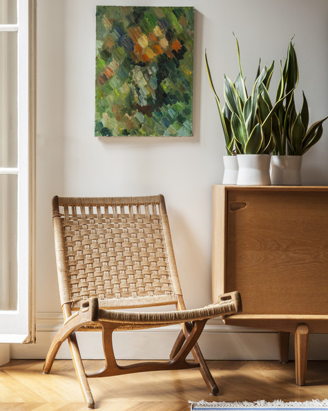 Scandinavian - A folding chair beside a wooden credenza
