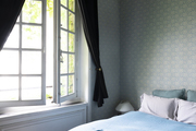 A bedroom with green printed wallpaper and French windows.