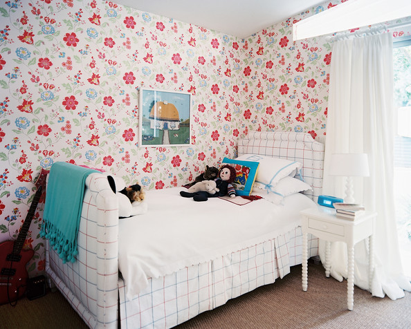 Stuffed Animals - A white upholstered bed accented by floral-patterned wallpaper and a blue throw