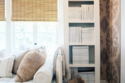 A daybed, white built-in bookcases, and patterned wallpaper in a study