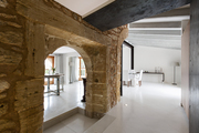 An arched stone doorway and exposed wood beams in a white dining area