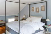 A serene blue bedroom with gray bedding
