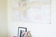A pastel painted art piece hanging above a collection of books, photographs, an sculptures.