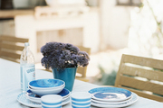 An outdoor dining area set with mix-and-match blue dishes