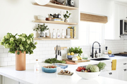 Fruits, vegetables, and accessories displayed in an all-white kitchen with subway tile.