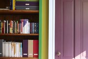 A green color blocked bookshelf next to a purple door