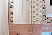 Albert Hadley's iconic fireworks-patterned wallpaper in a bathroom with pink tile