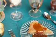 Tarte tatin with caramel sauce on a table set with a blue velvet tablecloth and horn flatware