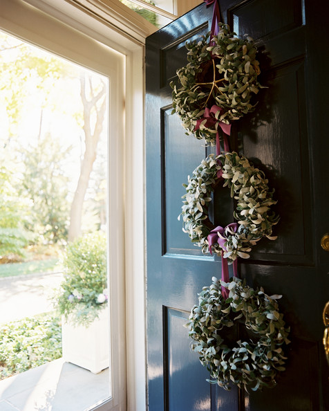 Traditional Holiday Decor - A black front door decorated with a trio of wreaths