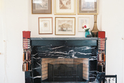 Framed art hung above a black marble mantel