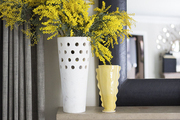 Bright yellow flowers on a gray mantel