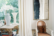 A leather chair with a leopard-print pillow beside an ornate console
