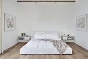 A white bed with floating nightstands.