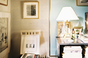A white chair with a striped seat beside a collection of framed art and a tripod table lamp