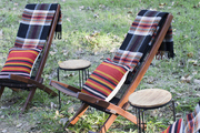 Some chairs around a fire with plaid blankets.