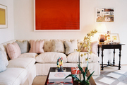 Red artwork hung above a tufted sectional couch