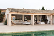 A pool house with outdoor furniture, opening onto a patio