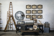 An industrial-style vignette at American Street Showroom with artwork and a mirror