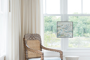 A Bohemian brown chair in front of white curtains.