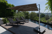 An outdoor patio with lounge chairs and an umbrella for shade.