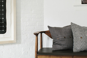 Patterned pillows atop vintage wooden bench.
