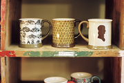 Aged wooden shelves covered with patterned mugs