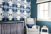A child's nursery with vibrant wallpapered walls.