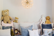 A Sputnik chandelier hangs over a child's daybed
