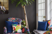 A brightly printed chaise lounge rests beneath a single palm tree