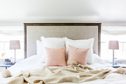 A neutral bed with pink throw pillows.
