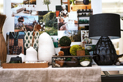 An inspiration board of images above a table topped with linen and a black lamp