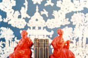 Glossy red bookends against blue-and-white pagoda-motif wallpaper