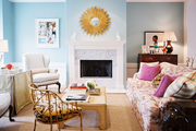 A floral couch, a pair of white wingback chairs, and a tiger-print occasional chair in a blue living room