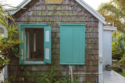 Pastel green shutters on a brown-shingled guest house