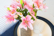 A detail of flowers in a vase next to some decor items.