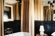 Camel-colored shower curtains and a freestanding tub in a black bathroom