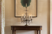 An antique console and crystal-and-bronze girandole in an entry