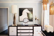 Artwork featuring a horse above a wood-and-white dresser with brass ring pulls
