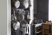 A galley kitchen makes use of vertical space for functional storage, with a wall painted in a steely hue.