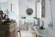 A round mirror and footed tub in a tile-walled bathroom