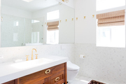 A contemporary bathroom with white walls and a red runner rug.