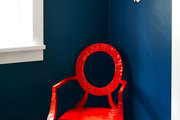 A Louis-style chair painted bright red in front of a blue-painted hallway wall