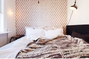 A bedroom with a tufted wallpaper headboard