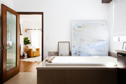 A wooden-based bathtub in a bathroom with white walls
